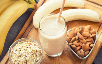 A glass of smoothie with bananas, nuts and oats on a chopping board